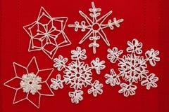 Vit virkade snöflingor på rött Royaltyfri Foto