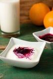 Vit yoghurt i en bunke med frukt som förläggas på den gröna tabellen royaltyfria foton