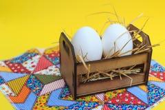 Vita ägg i en träspjällåda, på en patchworkfilt, med gul bakgrund arkivbilder