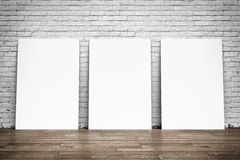 Vita affischer på tegelstenväggen och trägolv Royaltyfri Fotografi