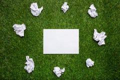 Vita ark av papper med cramled ark på gräset Arkivbild