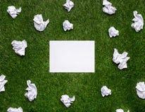 Vita ark av papper med cramled ark som ligger på gräset Arkivbilder