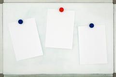 Vita ark av papper som fästas till det gamla smutsiga magnetiska brädet w Royaltyfria Bilder
