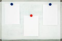 Vita ark av papper som fästas till det gamla smutsiga magnetiska brädet w Arkivbild