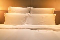 Vita ark gör till kung formatsäng med dubbla kuddar med varmt ljus fotografering för bildbyråer