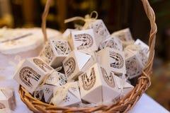Vita askar för gästen som deltar i bröllopet i korgen Formade favörer huset som innehåller konfettier Bonbonniere Arkivfoto