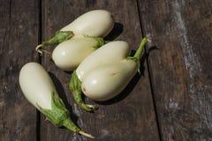 Vita aubergine på en gammal trätextural bakgrund fotografering för bildbyråer