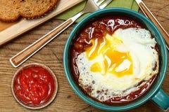 Vita bönor i tomatsås över det lätta ägget med rostat bröd och ketchup Royaltyfri Bild