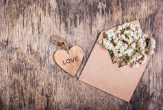 Vita blommor i ett pappers- kuvert och en trähjärta St Dag för valentin` s Bakgrunder och mallar Arkivfoto