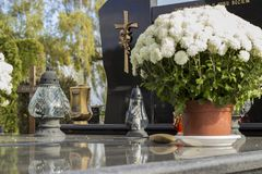 Vita blommor, lampions och grav Arkivbilder