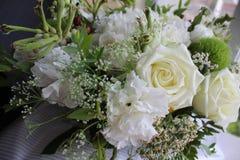 Vita blommor nära fönstret arkivbild