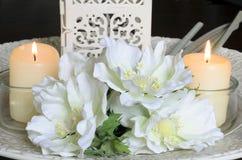 Vita blommor och stearinljus på Arkivfoton