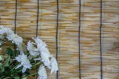 Vita blommor som förläggas på vävde rullgardiner 1 för ett trä Royaltyfria Foton