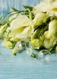 Vita blommor som ligger på ett blått träbräde Arkivfoton