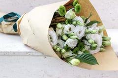 Vita blommor som slås in i papper Arkivbild
