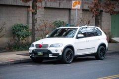 Vita BMW som dekoreras i julprydnader royaltyfria foton