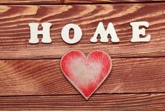 Vita bokstäver med ordet HEM och hjärta på träbakgrund royaltyfria foton