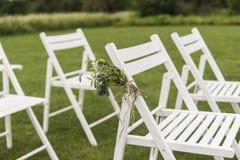 Vita bröllopstolar dekorerade med nya blommor på ett grönt gräs Tomma trästolar för gäster på grön gräsmatta i arkivfoto