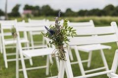 Vita bröllopstolar dekorerade med nya blommor på ett grönt gräs Tomma trästolar för gäster på grön gräsmatta i royaltyfria foton