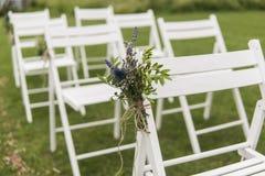 Vita bröllopstolar dekorerade med nya blommor på ett grönt gräs Tomma trästolar för gäster på grön gräsmatta i royaltyfri fotografi