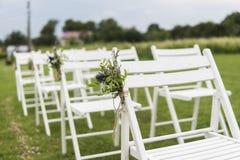 Vita bröllopstolar dekorerade med nya blommor på ett grönt gräs Tomma trästolar för gäster på grön gräsmatta i arkivbilder