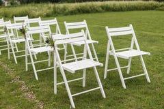 Vita bröllopstolar dekorerade med nya blommor på ett grönt gräs Tomma trästolar för gäster på grön gräsmatta i royaltyfria bilder
