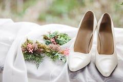 vita brud- skor och blom- garneringar Arkivbilder