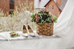 vita brud- skor och blommor i korgen Arkivfoto