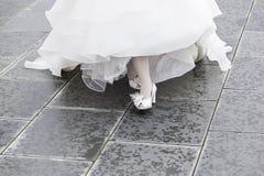 Vita brud- skor på ett bröllop Arkivfoton