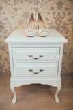 Vita brud- skor på träbyrån Royaltyfri Foto