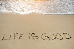 Vita in buon scritto sulla spiaggia di sabbia - concetto di pensiero positivo Fotografia Stock
