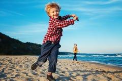 Vita Caucasian barn lurar vänner som spelar att köra på havhavsstranden på solnedgång utomhus Royaltyfri Fotografi