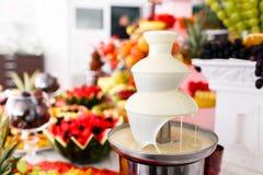 Vita chokladspringbrunn och frukter för efterrätt på brölloptabellen arkivbilder