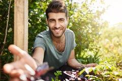 Vita della campagna, naature Chiuda sul ritratto all'aperto di giovane uomo caucasico barbuto attraente nel sorridere blu della m Fotografia Stock