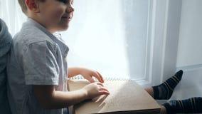 Vita della gente cieca, leggente il libro di Braille dal ragazzo cieco sul davanzale stock footage