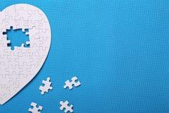 Vita detaljer av ett pussel på en blå bakgrund Ett pussel är en pu Fotografering för Bildbyråer