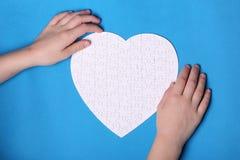 Vita detaljer av ett pussel på en blå bakgrund Ett pussel är en pu Royaltyfria Bilder
