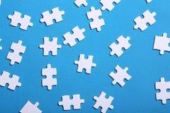 Vita detaljer av ett pussel på en blå bakgrund Ett pussel är en pu Royaltyfri Foto