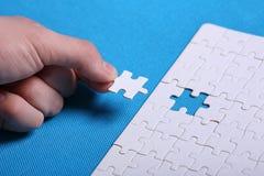 Vita detaljer av ett pussel på en blå bakgrund Ett pussel är en pu Arkivfoton