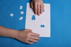 Vita detaljer av ett pussel på en blå bakgrund Ett pussel är en pu Royaltyfri Bild