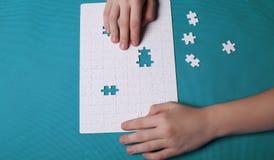 Vita detaljer av ett pussel på grön bakgrund Ett pussel är en puz Arkivfoton