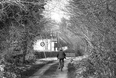 Vita di paese Una donna su una bicicletta con il suo cane che entra in un villaggio rurale nella campagna inglese, Regno Unito Immagine Stock Libera da Diritti