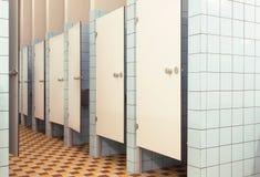 Vita dörrar i minimalistic inre av det offentliga badrummet med toalettbås Fotografering för Bildbyråer