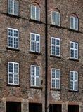 Vita fönsterramar i bruna tegelstenväggar Arkivfoto