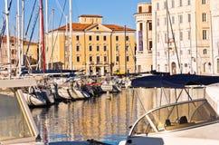 Vita fartyg, blå himmel och färgrika byggnader på Piran härbärgerar, Istria Arkivbild