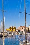 Vita fartyg, blå himmel och färgrika byggnader på Piran härbärgerar, Istria Royaltyfria Bilder