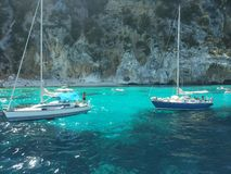 Vita fartyg i det blåa havet av ‹sardinia för †med imponerande föreställning vaggar arkivbild