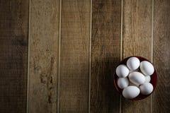 Vita fega ägg, inom en bunke, på en trätabell Top beskådar royaltyfri fotografi