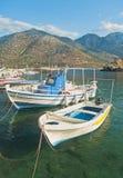 Vita fiskebåtar i liten bergig hamn Royaltyfria Bilder