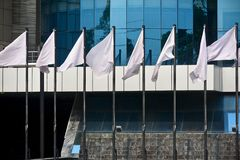 Vita flaggor framme av ett modernt arkitektoniskt byggnadsfotografi Arkivfoto